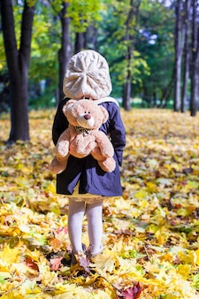 Retrovisione della bambina affascinante con uno zaino-orso dietro nella foresta soleggiata di autunno