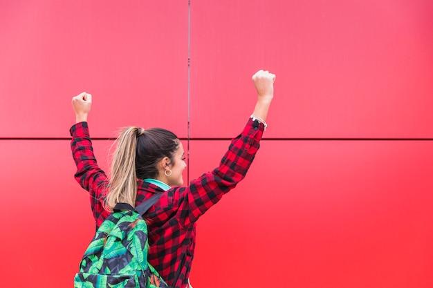 Retrovisione della borsa di trasporto dell'adolescente alla parte posteriore che solleva le loro mani contro il fondo rosso