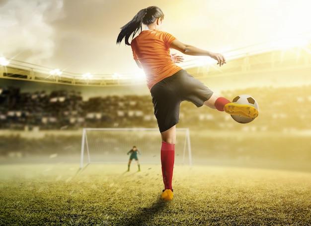 Retrovisione della donna asiatica del giocatore di football americano in maglia arancio che dà dei calci alla palla nella casella di rigore