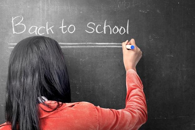 Retrovisione della donna asiatica dello studente che scrive di nuovo alla scuola sulla lavagna