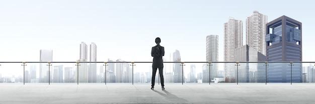 Retrovisione della donna asiatica di affari che sta sul terrazzo moderno e che esamina vista