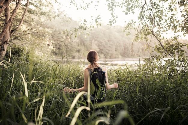 Retrovisione della donna che cammina nell'erba verde vicino al lago