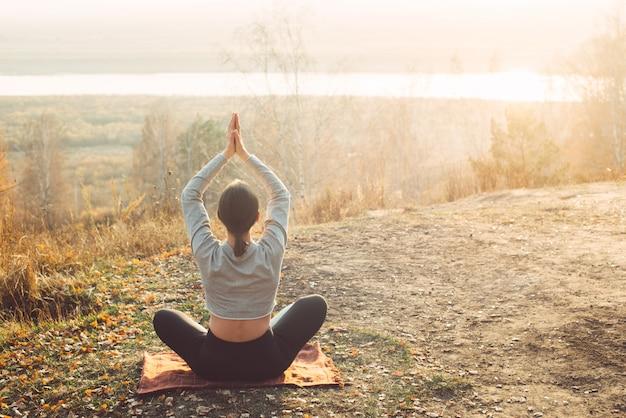 Retrovisione della donna che medita nella posizione di loto di mattina sulla natura.