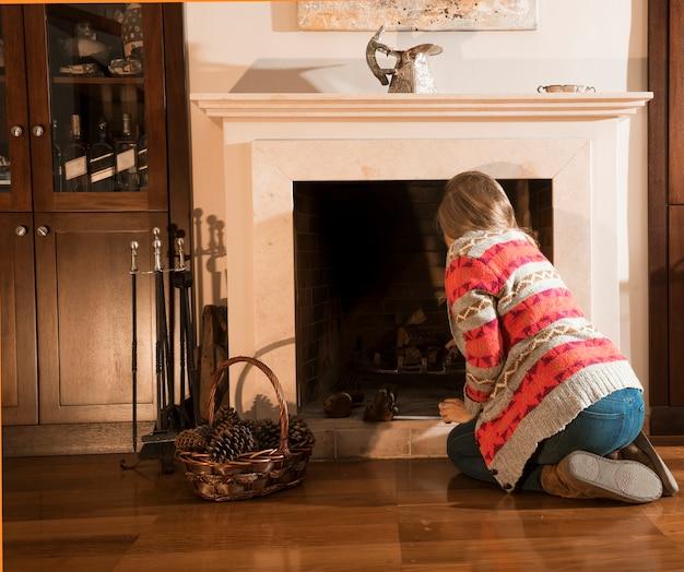 Retrovisione della donna che sistema legna da ardere nel camino a casa