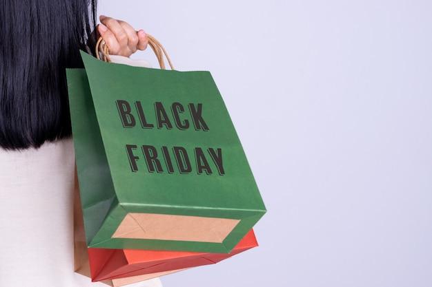 Retrovisione della donna che tiene il sacchetto della spesa di black friday. concetto di black friday con lo spazio della copia.
