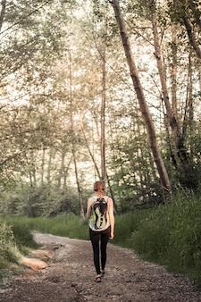 Retrovisione della donna con il suo zaino che cammina sulla traccia della foresta