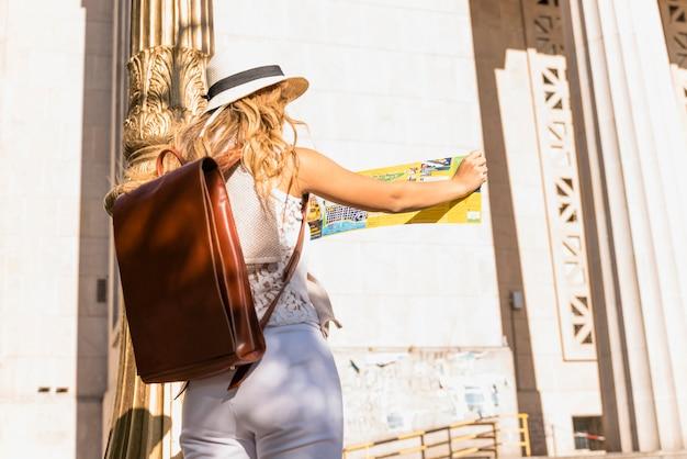 Retrovisione della giovane donna che porta borsa di cuoio che esamina mappa