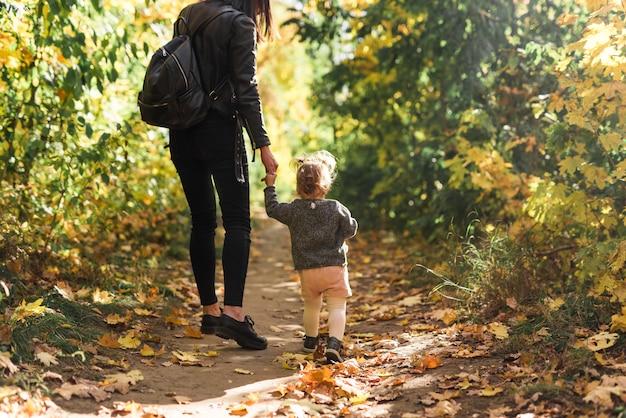 Retrovisione della madre e della figlia che camminano nella foresta