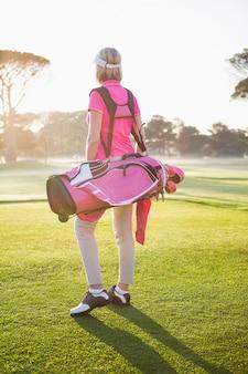 Retrovisione della sportiva che tiene una sacca da golf