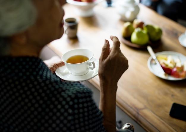 Retrovisione della tazza di tè asiatica senior della tenuta della donna che parla con gli amici