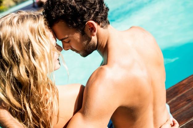 Retrovisione delle coppie che si siedono dalla piscina naso a naso