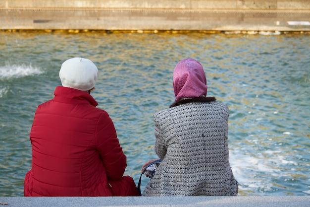 Retrovisione di due donne anziane che si siedono su una panchina dal canale in un parco cittadino