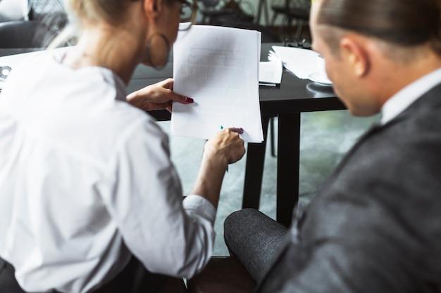 Retrovisione di due persone di affari che esaminano documento nel caf�