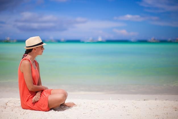 Retrovisione di giovane donna sexy in cappello che si siede sulla spiaggia di sabbia bianca