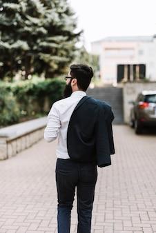 Retrovisione di giovane uomo d'affari con il cappotto sopra la sua spalla