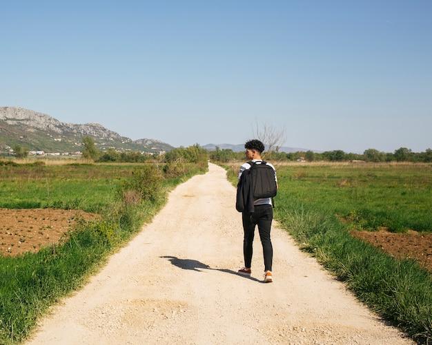 Retrovisione di giovane viaggiatore maschio che cammina nello zaino di trasporto del lato del paese
