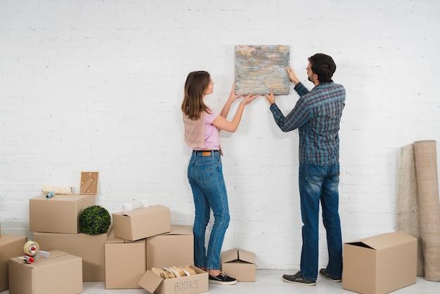 Retrovisione di giovani coppie che dispongono una cornice sulla parete bianca con le scatole di cartone