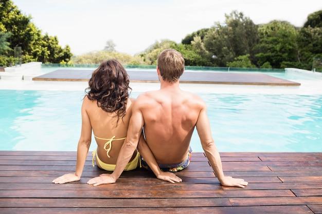 Retrovisione di giovani coppie che si siedono dal poolside un giorno soleggiato