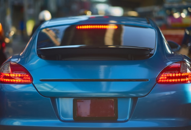 Retrovisione di nuova automobile sportiva sul fondo della via del traffico