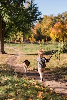 Retrovisione di piccola ragazza che cammina con il suo cane nella foresta traccia