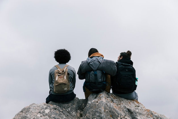 Retrovisione di tre amici che si siedono sulla roccia contro il cielo