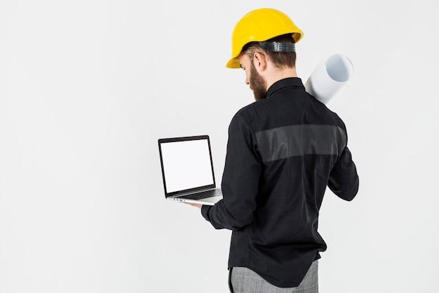 Retrovisione di un architetto maschio che esamina computer portatile sopra i precedenti bianchi