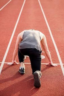 Retrovisione di un atleta maschio che prende posizione sulla pista di corsa rossa per correre