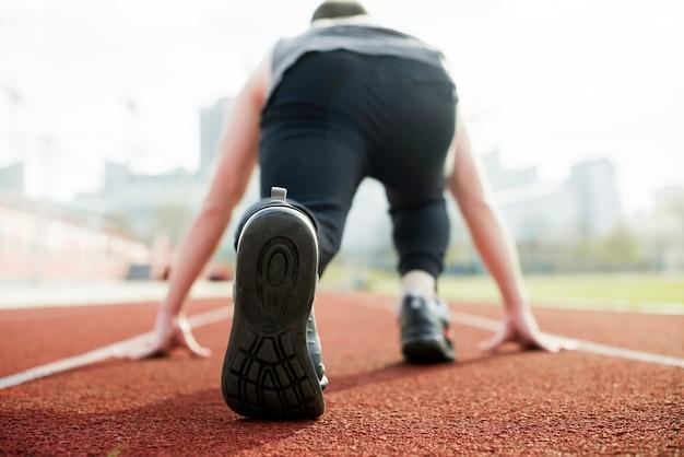 Retrovisione di un atleta maschio che prende posizione sulla pista di corsa rossa