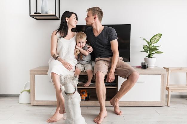 Retrovisione di un cane che esamina coppia che se lo guarda che si siede con il loro figlio davanti alla televisione