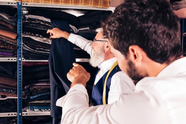 Retrovisione di un dito puntato dell'uomo allo stilista senior che prende tessuto dallo scaffale