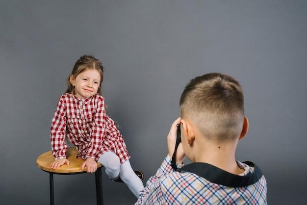 Retrovisione di un ragazzo che prende immagine di una ragazza sorridente che si siede sulle feci dalla macchina fotografica