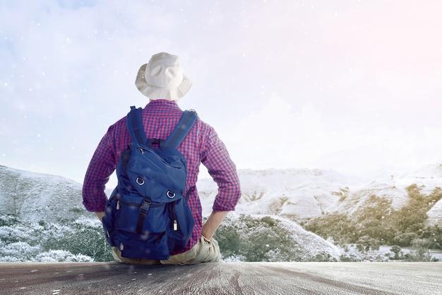 Retrovisione di un uomo asiatico in un cappello con uno zaino che si siede sul pavimento di legno e che esamina la montagna nevosa