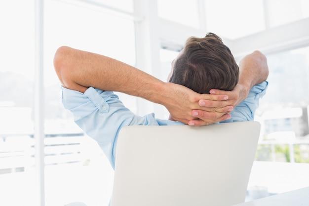 Retrovisione di un uomo casuale che riposa con le mani dietro la testa in ufficio