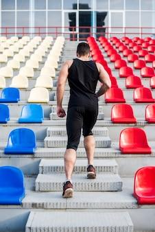 Retrovisione di un uomo che corre su per le scale sulla gradinata