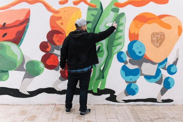 Retrovisione di un uomo che fa i graffiti con la latta di spruzzo sulla parete