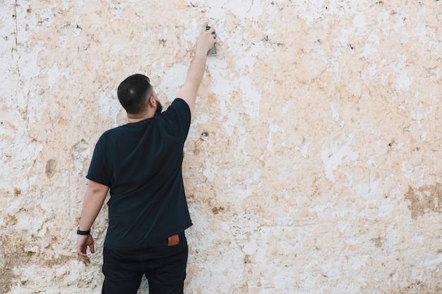 Retrovisione di un uomo che fa i graffiti sulla parete sbucciata