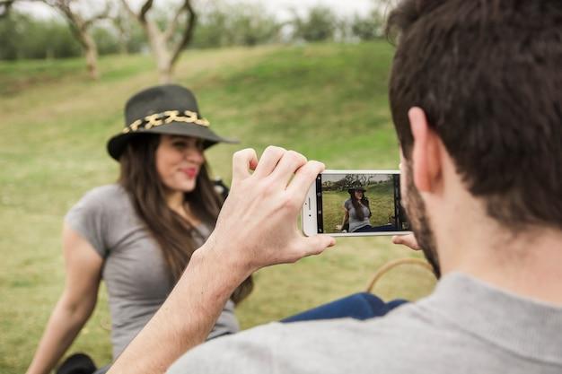 Retrovisione di un uomo che prende immagine della sua ragazza che si siede nel parco
