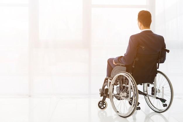 Retrovisione di un uomo d'affari che si siede sulla sedia a rotelle che esamina finestra