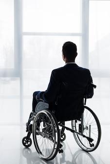 Retrovisione di un uomo d'affari in vestito che si siede sulla sedia a rotelle che esamina finestra