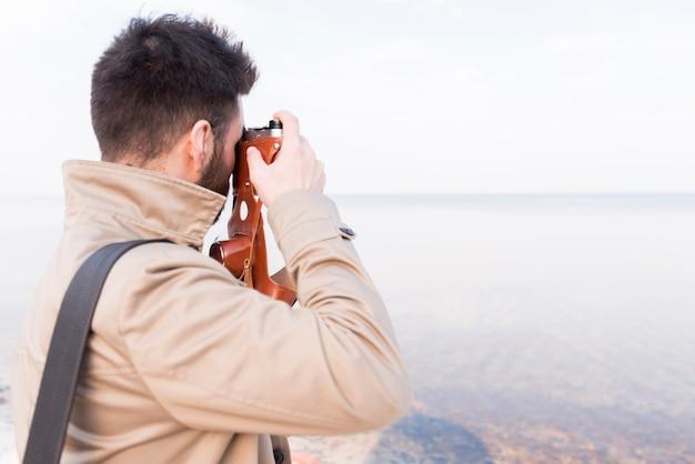 Retrovisione di un viaggiatore maschio che prende immagine del mare idilliaco con la macchina fotografica