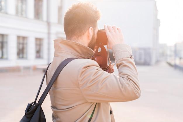 Retrovisione di un viaggiatore maschio che prende l'immagine nella città con la macchina fotografica