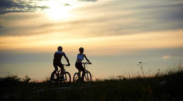 Retrovisione di una coppia di ciclisti che guidano lungo la strada fra l'erba