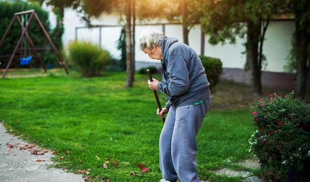 Retrovisione di una donna anziana che pulisce con una scopa nel cortile della casa.