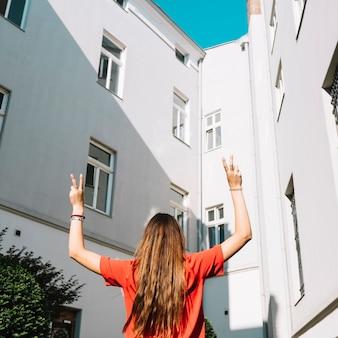 Retrovisione di una donna che fa gesto di pace vicino a costruzione