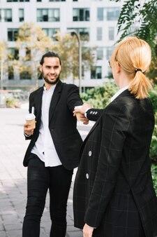Retrovisione di una donna di affari che prende la tazza di caffè da asporto dalla mano dell'uomo sorridente