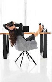 Retrovisione di una donna di affari che si siede sulla sedia che si rilassa alla scrivania