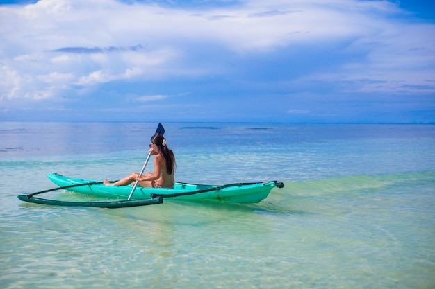 Retrovisione di una giovane donna che kayaking nel mare blu libero