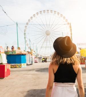 Retrovisione di una giovane donna davanti alla parete gigante al parco di divertimenti
