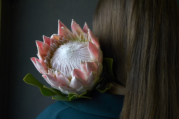 Retrovisione di una ragazza con capelli scuri che tengono un fiore rosa del protea su un fondo scuro, fuoco selettivo