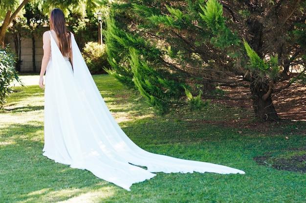 Retrovisione di una sposa in vestito lungo bianco che cammina nel parco
